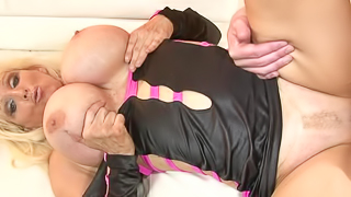 A hot milf is getting cum all over her large fake silicone filled tits